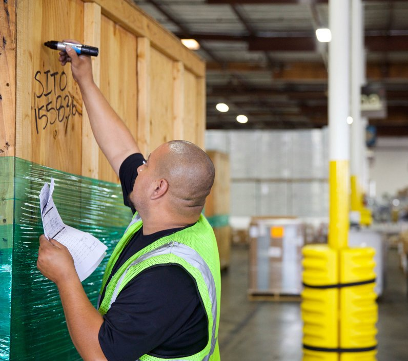 warehouse worker writing on crate