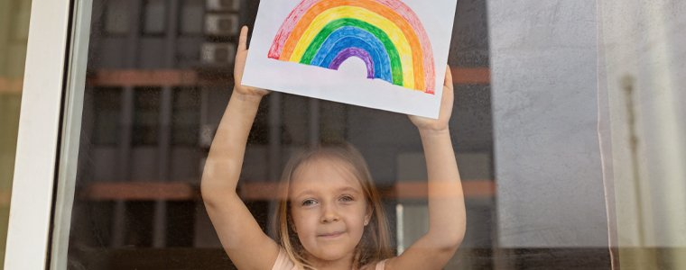 young girl with rainbow drawing