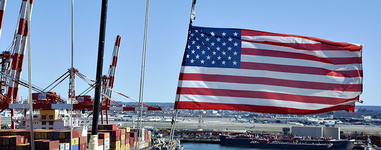American Flag at a shipping yard with cranes in background